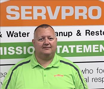 Man wearing a bright green shirt standing in front of a SERVPRO sign on white wall.