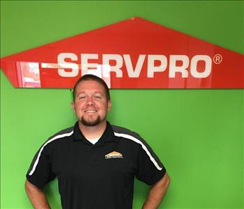 Man wearing a black polo standing in front of green wall with SERVPRO sign