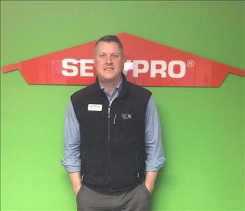 Man standing in front of a SERVPRO sign wearing a black vest