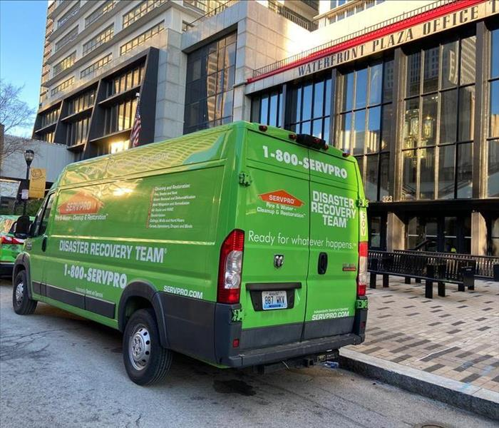 SERVPRO green van parked on the street in front of a downtown Louisville building following a fire and water damage.
