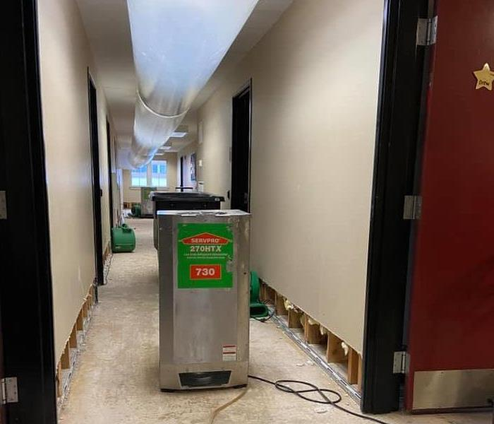 Hallway in dormitory with flooring remove, plastic tubing overhead and a grey dehumidifier.